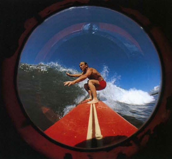 Dewey Weber at Haleiwa, 1967. This is one of my first fish eye camera board efforts. I used strips of inner tube to hold the camera to the board. You can see the inside of the lens port in these earlier images. Dewey held a strong with a little block of wood on the end. When he pulled, that activated the camera to fire off an entire roll of 36 exposures.