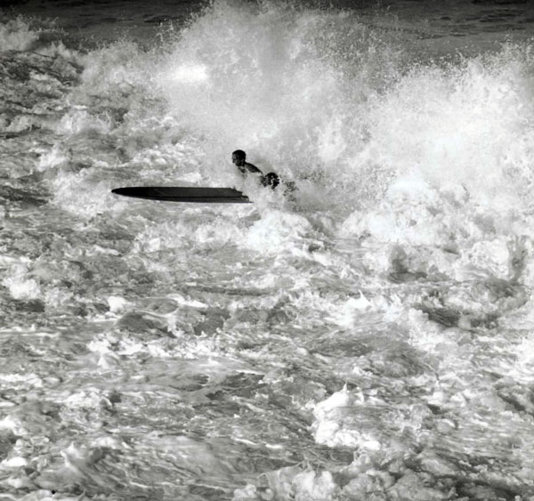 Pete Peterson on a huge west swell day during the Winter of '39. He tried for an hour to get out and never did make it. Here he's caught in the backwash - trying to ride it out.
