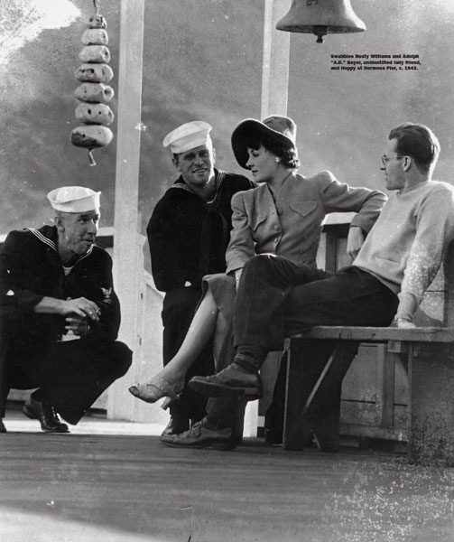 """Swabbies Rusty Williams and Adolph """"A.D."""" Bayer, unidentified lady friend, and Hoppy at Hermosa Pier, c. 1943."""