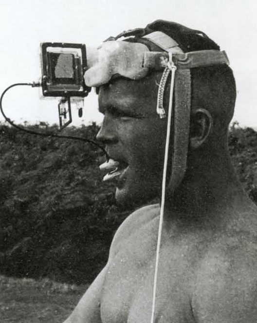"""Buzzy Trent with experimental camera rig. I kept trying new angles and thought of this helmet setup. I did a casting out of acrylic resin in my dental office to hang the camera on, it was a tiny spring-wound Tessina that would take twelve shots with a single wind. The cable release was embedded in a mouthpiece, activated by """"dental power"""" of which fuzzy had an ample supply. It turned out to be awkward and not a wide enough angle for framing."""