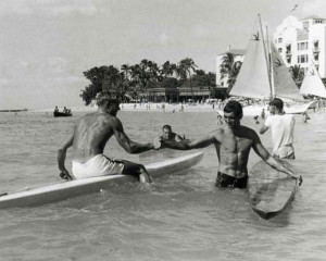 """George Downing congratulating Tommy Zahn at the finish. Zahn had been trying to beat Georgie for 3-4 years and he had finally won, which he largely attributed to this Quigg """"Stradivarius racing board,"""" build of balsa with ribs and paper-thin skin like an airplane wing. That's Bud Browne filming Tom Volk in the background."""